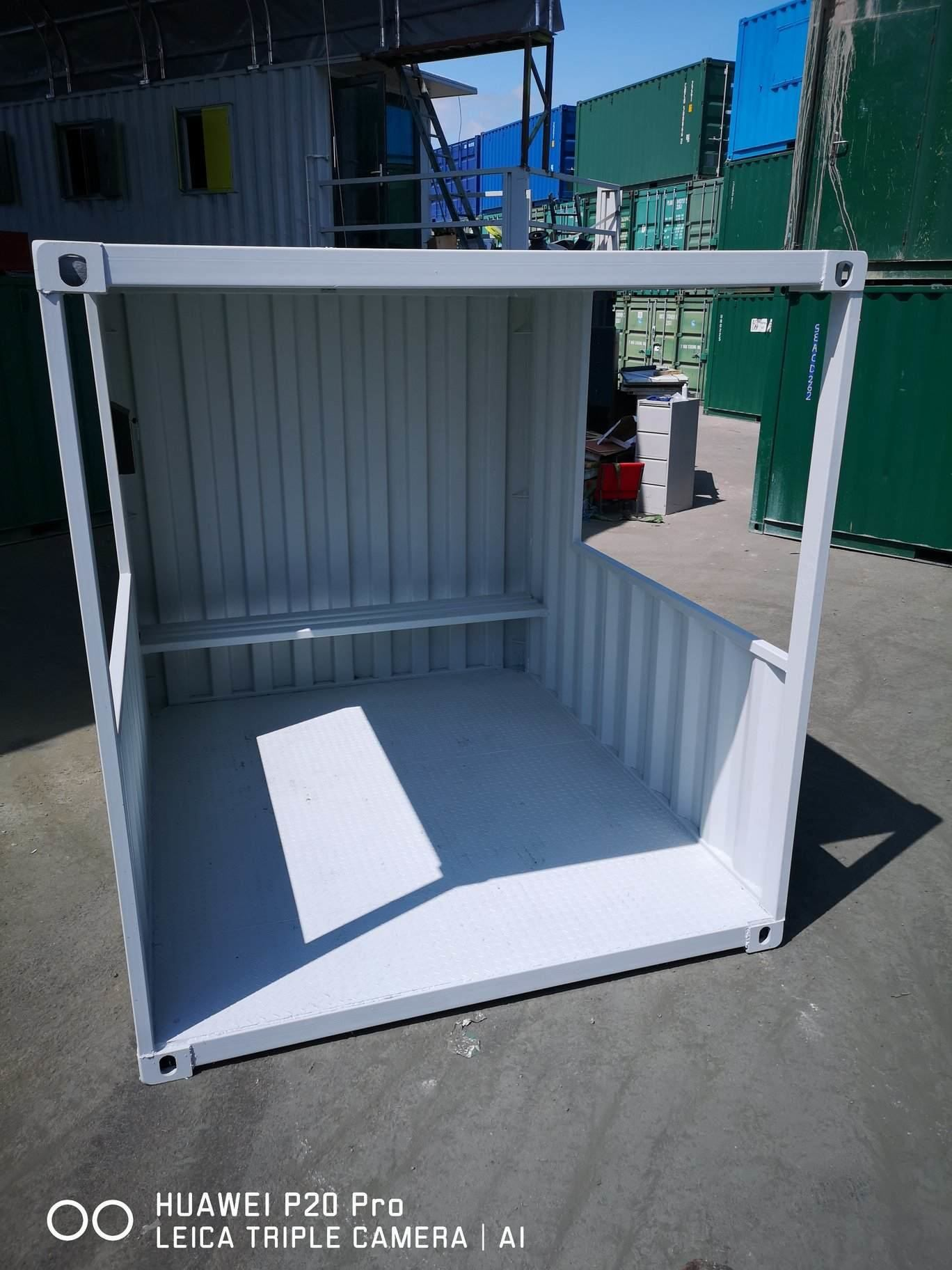 Grey portable smoking shelter in storage container yard