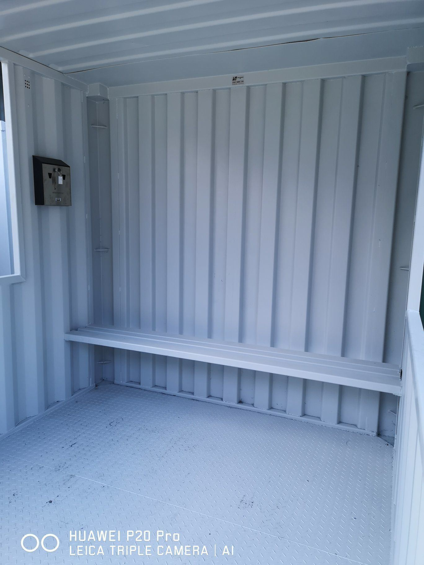 Inside of smoking shelter container with bench and cigarette bin