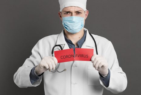 Doctor with face mask tearing red card that says coronovirus