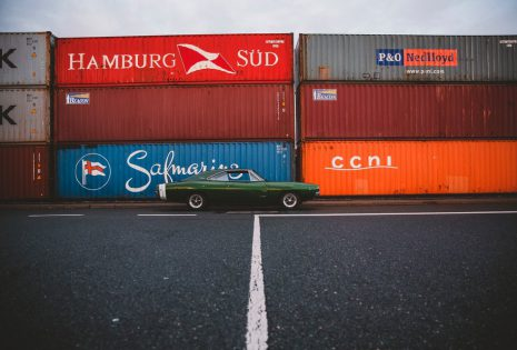 Green car next to multiple stacked shipping containers